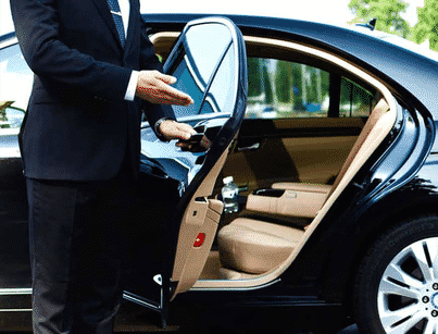 Chauffeur Opening rear door of Black Sedan at Edmonton Airport for Aiport Limo Transfer Service